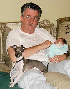 man with dog and newborn baby.