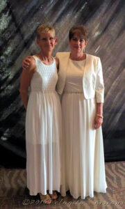 two women dressed in formal wear