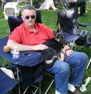 man sitting in camp chair with German Shepherd puppy laying in his lap